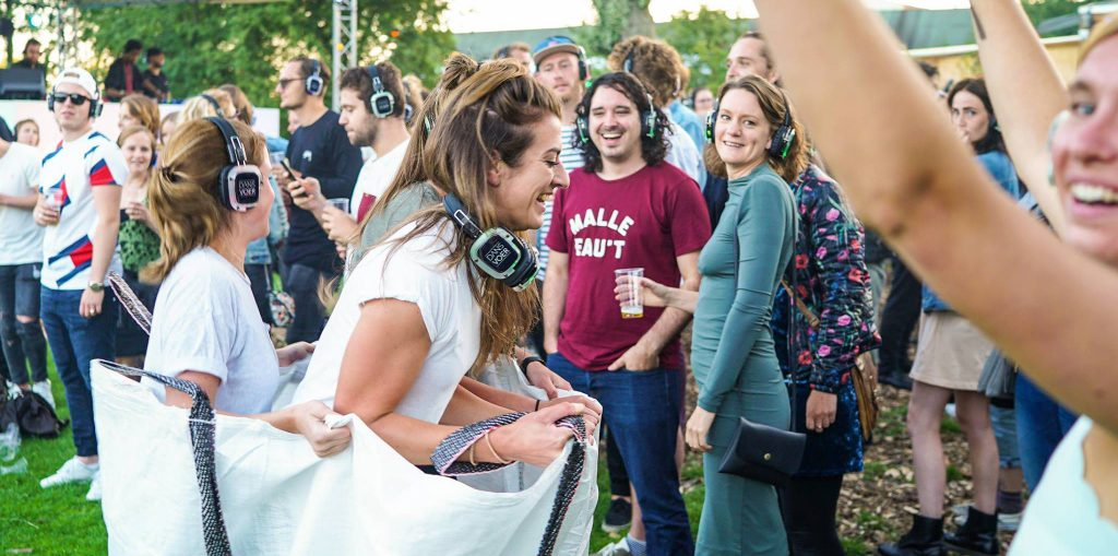 Bezoekers van DANSVOER Silent Disco in het Vroesenpark doen mee aan een wedstrijdje zaklopen