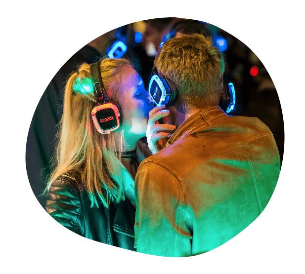 Foto van twee bezoekers van een DANSVOER Silent Disco evenement. Kleurrijk verlichte scene waarbij de man zijn koptelefoon van zijn oor schuift om te kunnen verstaan wat de vrouw tegen hem zegt.
